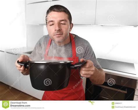 cuisine de homme 224 la maison dans le tablier de cuisinier tenant le pot appr 233 ciant faisant