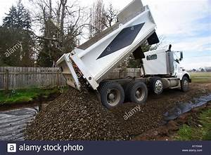 Dump truck pours a load of gravel on a new road Stock ...