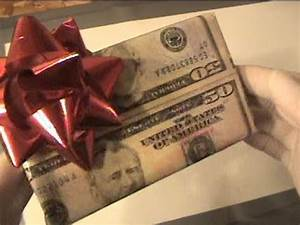 Wrapping a Christmas t with Real 50 dollar bills