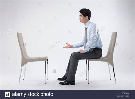 A Business Man Sitting And Talking To An Empty Chair Stock