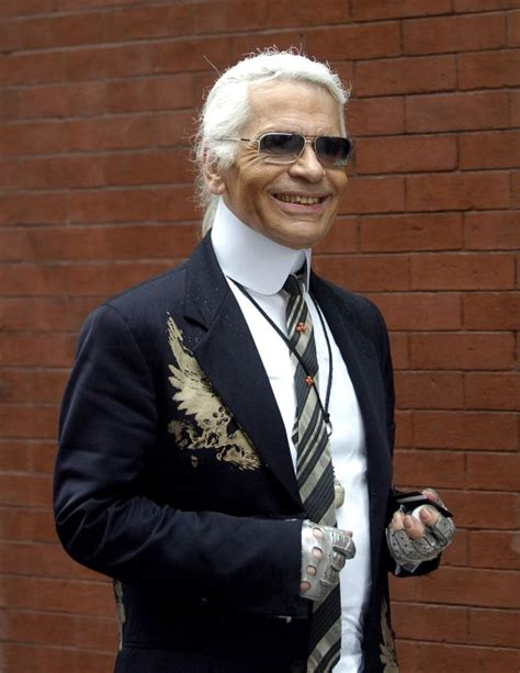 Karl Lagerfeld unveils missing tooth at Paris' Christmas ...