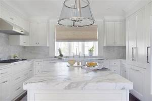 white u shaped kitchen with marble slab backsplash With kitchen colors with white cabinets with large sun face wall art