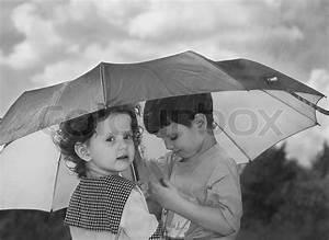 Little girl and boy hiding under an umbrella from the rain ...