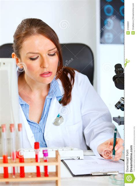Busy Female Medical Doctor Working At Her Office Stock