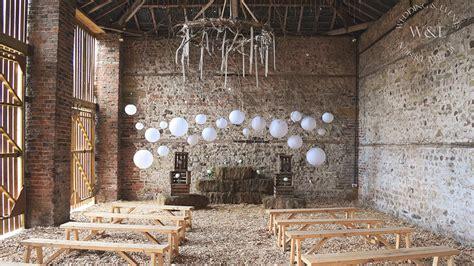 white hanging lanterns add style to a rustic barn wedding hanging lantern company