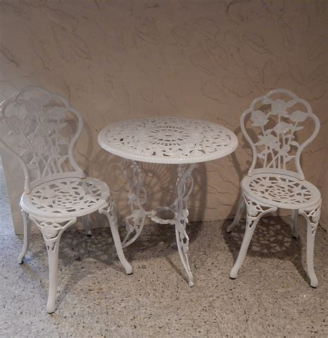 white painted cast iron bistro table and two chairs ebth