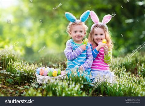 on easter egg hunt blooming stock photo 375166522 271   stock photo kids on easter egg hunt in blooming spring garden children with bunny ears searching for colorful 375166522