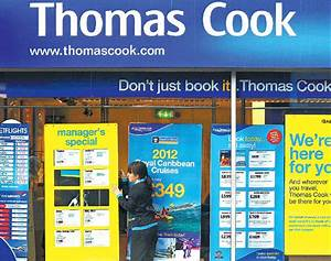A Worker Changes The Window Display Of Thomas Cook In
