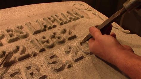 carving a raised letter inscription into granite for a