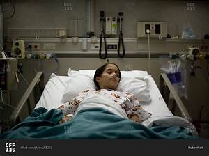 Young girl sleeping in hospital bed stock photo - OFFSET
