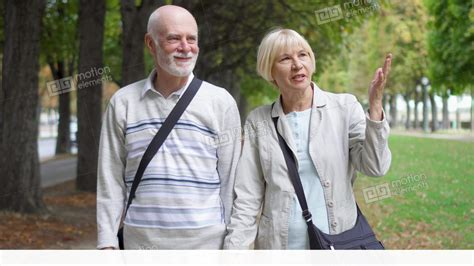 Senior Couple Walking In Park. Active Modern Life After