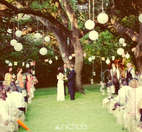 lanterns hung from tree branches afloral com wedding blog