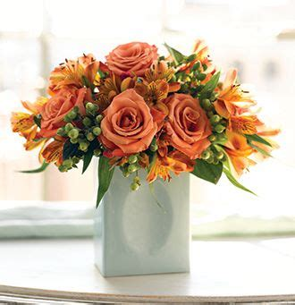 light orange roses with bright orange flowers arrangement with green vase jpg
