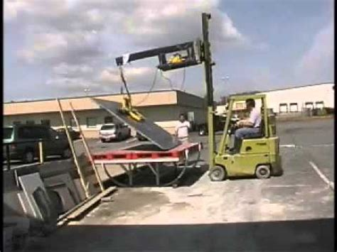 green forklift attempts to lift a slab of granite