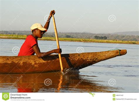 young malagasy african boy rowing traditional canoe