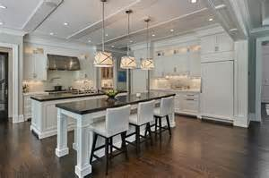 white kitchen with island side by side white kitchen islands with honed black marble countertops transitional kitchen