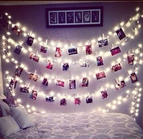 polaroid pictures hanging from lights by pegs
