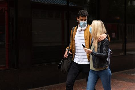 Young couple wearing face masks walking on the streets ...