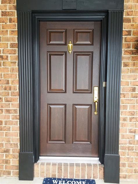 brown front door paired  brass hardware black trim