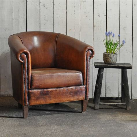 vintage worn leather club chair with arms