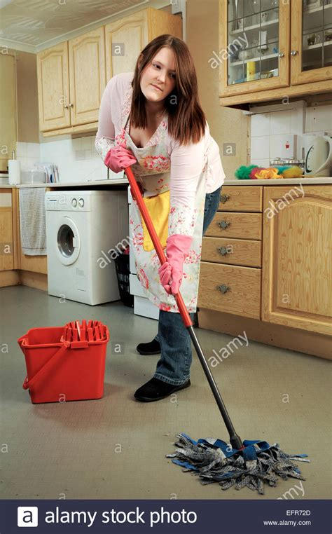 cleaning houses under the table young woman house wife cleaning her kitchen mopping the