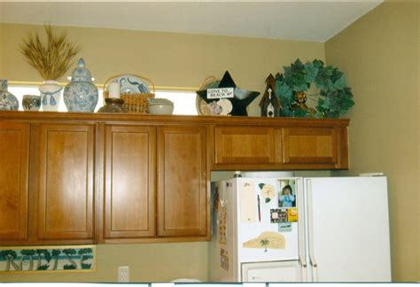 above kitchen cabinet decor decorating above kitchen cabinets ideas afreakatheart