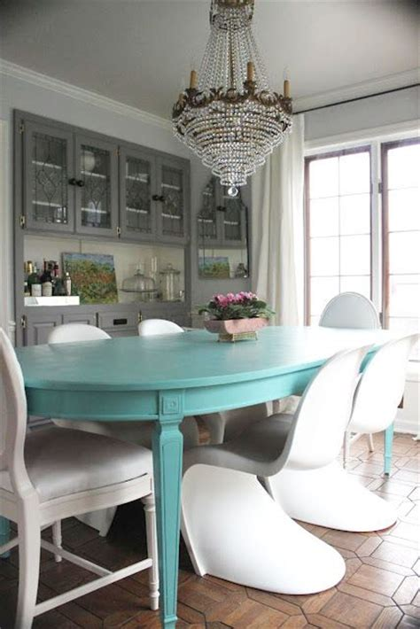 turquoise table paired with white chairs and grey walls
