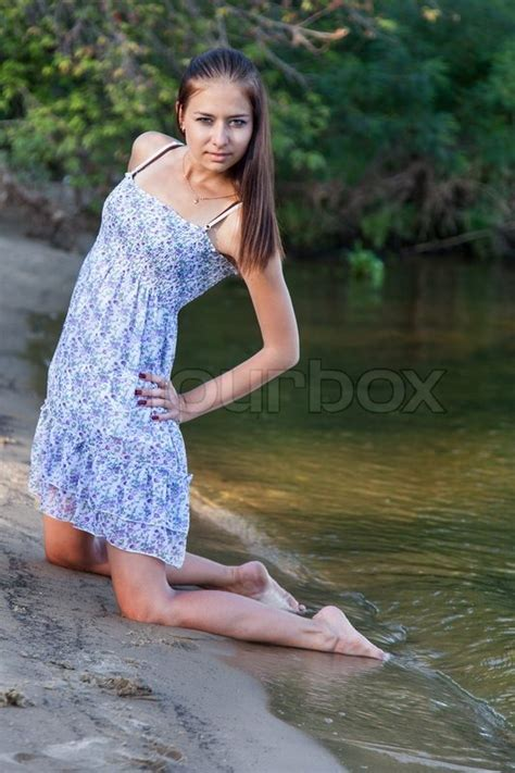 Young woman kneeling on beach   Stock Photo   Colourbox