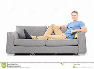 Relaxed Young Man Sitting On A Comfortable Sofa Stock ...