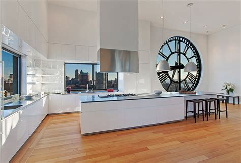 open plan white wood kitchen clock tower apartment glossy white open plan kitchen with island range and wood flooring