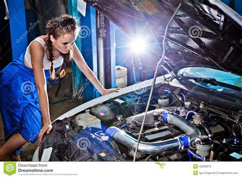 female auto mechanic repairing  car stock photo image