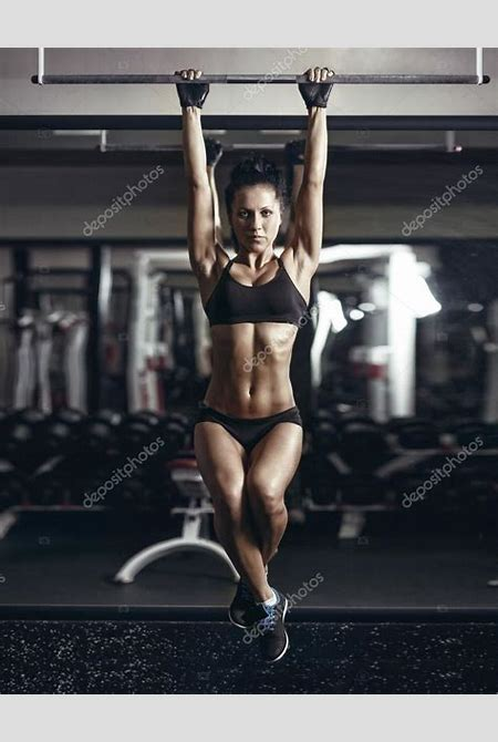 Sexy young fitness girl pulls up in the gym. Brunette fitness woman in black sport wear with ...