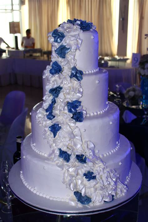 4 layer white wedding cake with cascading white and navy