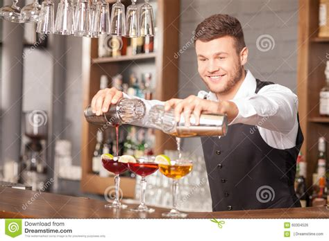Attractive Young Barman Making Drinks Pub Stock