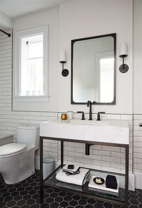 modern black and white bathroom is lit by modern taper