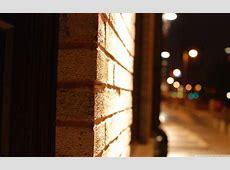 Brick wall close up blurry street at night