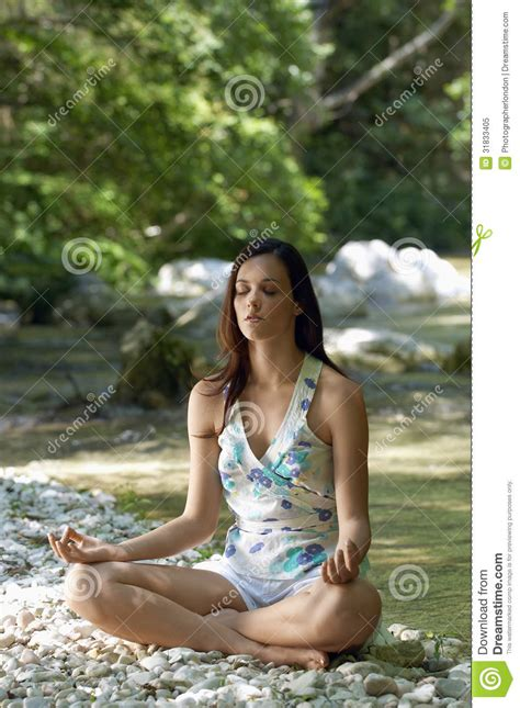 woman meditating lotus position forest river stock