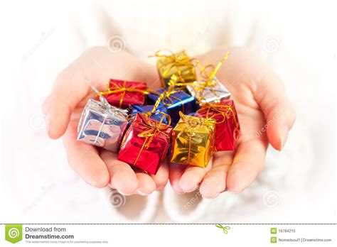 small christmas gifts in palms of hands stock photo