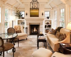 airy yet cozy living room with limestone fireplace flanked by built ins and leaded glass windows