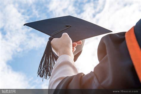 天空下拿着黑色流苏博士帽的毕业生高清图片 - 素材中国16素材网