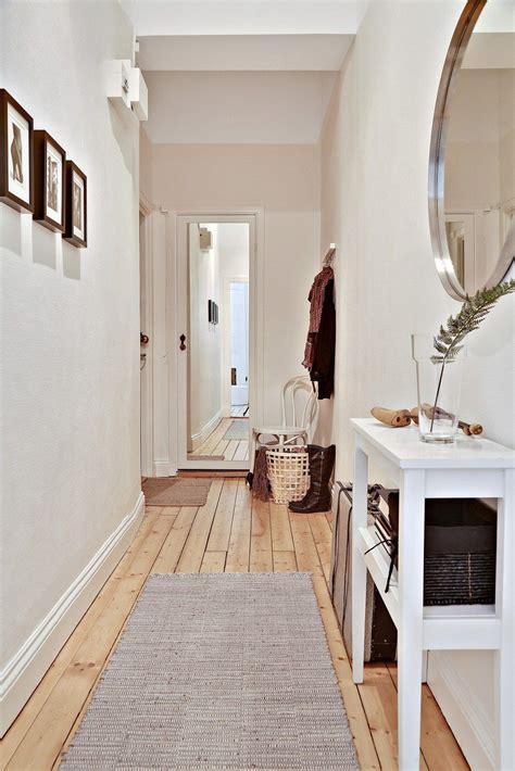 couloir dentree dun appartement blanc bois cadres sur