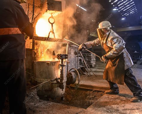 Worker pouring molten metal in foundry - Stock Image ...
