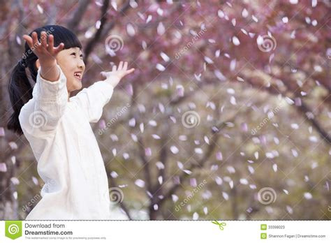 happy young girl throwing cherry blossom petals   air