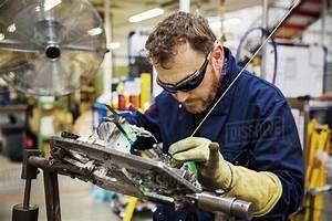 Male skilled factory worker wearing eye protectors welding ...
