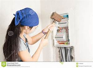 Woman Taking Aim At An Electrical Fuse Box Stock Photo