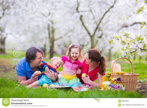 Family Enjoying Picnic In Blooming Garden Royaltyfree
