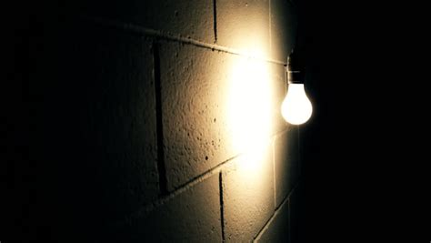 light bulb swaying against wall in room stock footage