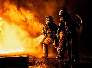 Two Firefighters Fighting Fire With A Hose And Water ...