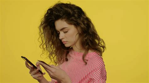 Unlike magstripe technology, it's highly secure. Young woman using mobile phone for online shopping with credit card in yellow studio. Beautiful ...