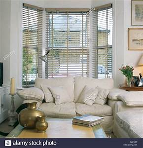 Cream sofa in front of bay window with slatted blind in for Couch and sofa table in front of window